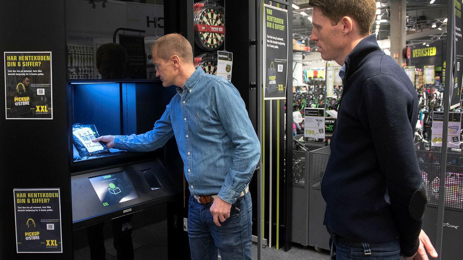 Klikk og hent er i ferd med å bli stor business for kjeder som XXL. Her viser it-direktør Espen Terland og XXL-sjef Tolle Grøterud (til høyre) hvordan pakkene kommer ut fra den nye roboten i butikken på Alnabru.