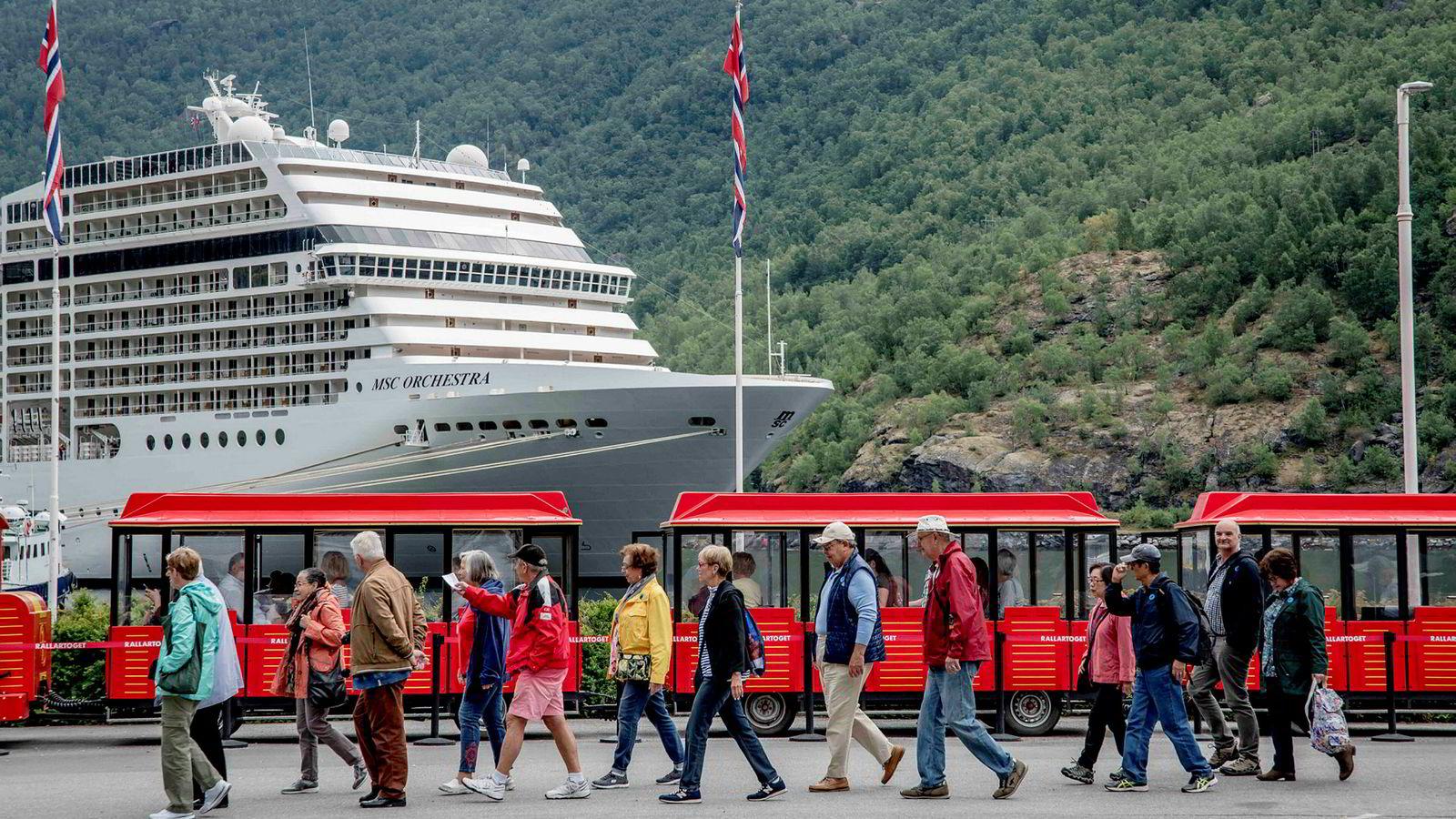 Et cruiseskip med 5000 gjester er et like stort fotavtrykk på miljøet som en by med 25.000 innbyggere. Her en gruppe turister foran et cruiseskip i Flåm.