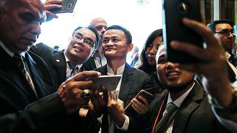 Alibaba-grunnlegger Jack Ma (i midten) må konstatere at «lillebror» har passert hans selskap i børsverdi. Foto: Mohd Rasfan/AFP/NTB Scanpix