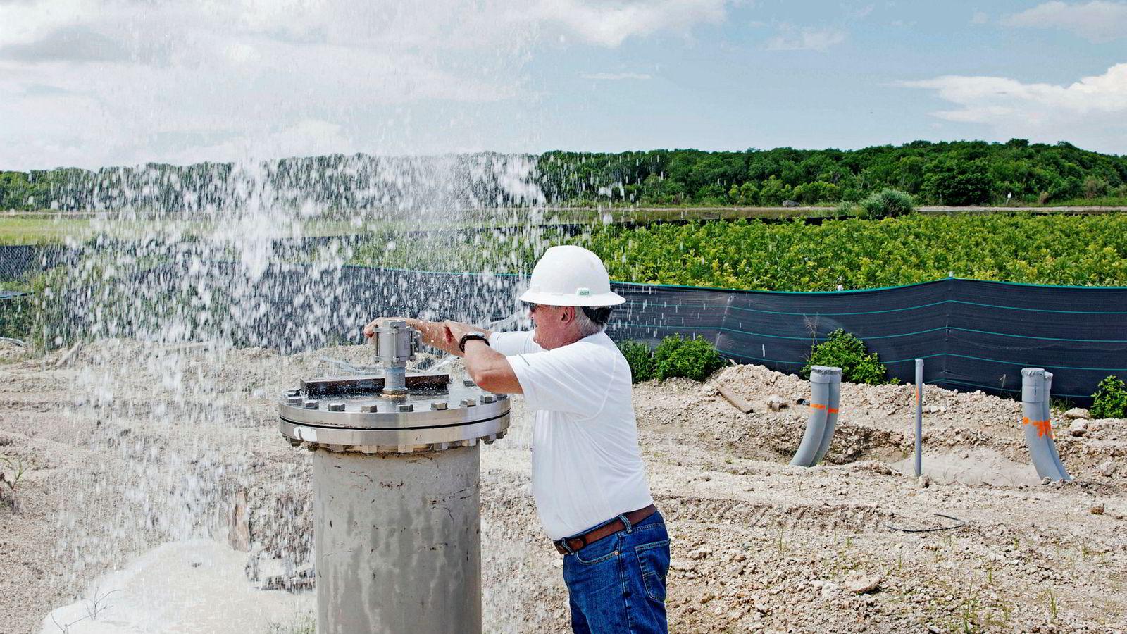 Vanngeolog Eric Meyer åpner en kran og salt grunnvann fra en dypvannsbrønn 700 meter under havnivå spruter ut over han og anlegget. Vannet har høyt trykk, noe som gjør at det ikke kan forurenses.