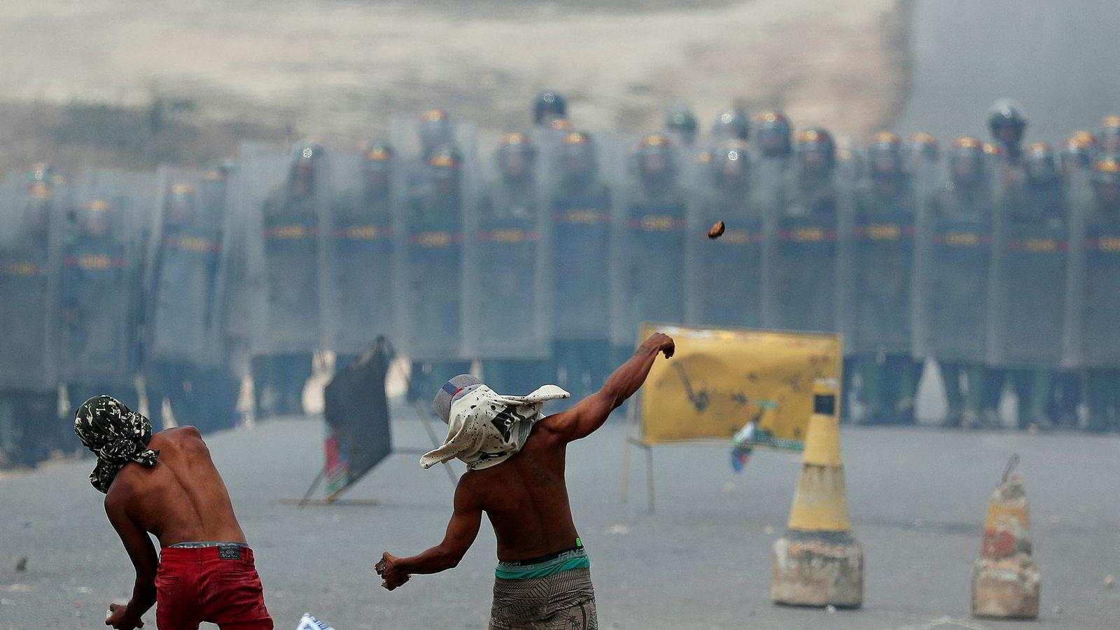 Demonstranter kaster stein mot nasjonalgarden ved grensen mot Pacaraima i Brasil. President Nicolás Maduro har stengt grensene, og samtidig har flere hundre venezuelanske soldater desertert.