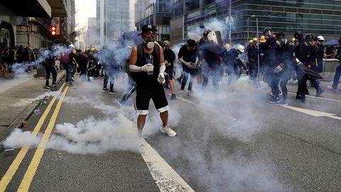 Flere hundre svartkledde demonstranter støtte lørdag sammen med opprørspoliti i Hongkong. Demonstrantene kastet brannbomber, stein og vannflasker mot politiet, som svarte med tåregass og køller.