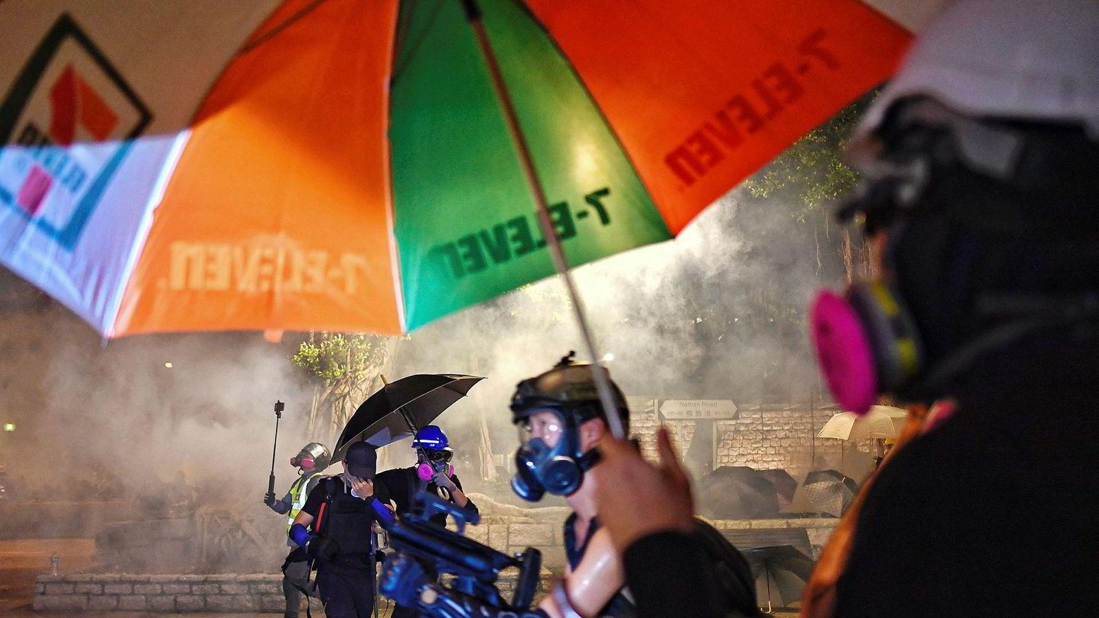 Både politi og demonstranter i Hongkong anklages for uakseptabel voldsbruk. Her bruker politiet tåregass for å spre demonstrantene utenfor politistasjonen Tsim Sha Tsui.