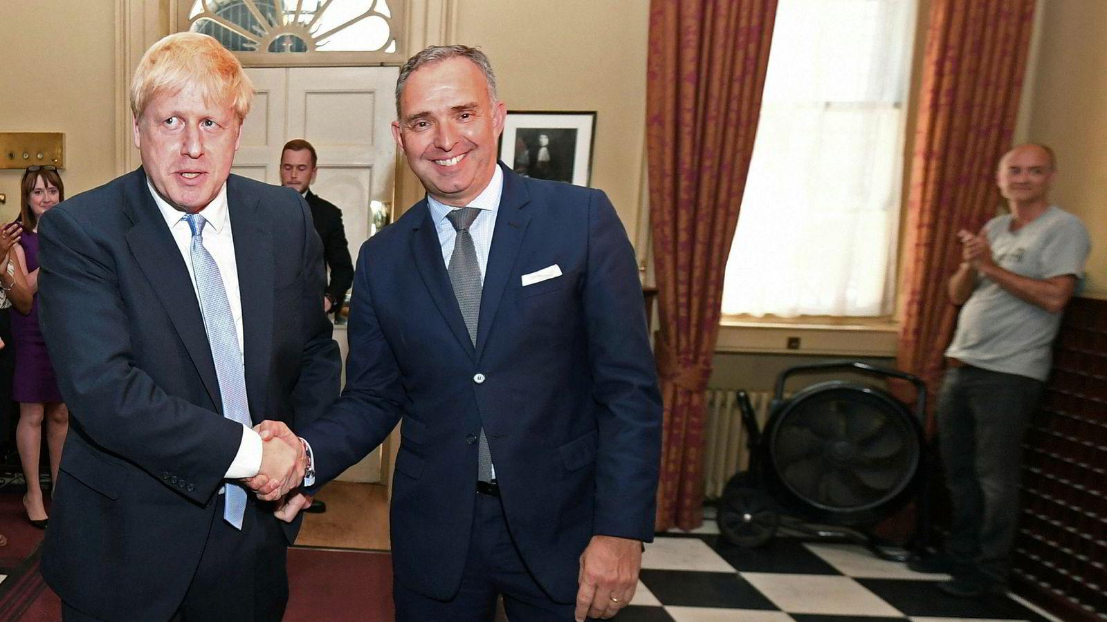 Statsminister Boris Johnson hilser på Sir Mark Sedwill, som er øverste byråkrat i Storbritannia, mens den omstridte rådgiveren Dominic Cummings står henslengt i bakgrunnen.