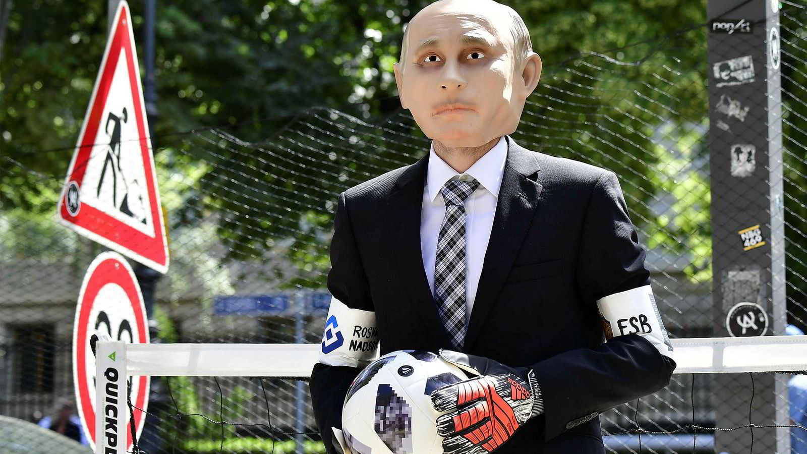 En demonstrant fra organisasjonen Reportere uten grenser har på seg en Vladimir Putin-maske foran den russiske ambassaden i Tyskland. Torsdag starter fotball-VM i Moskva.