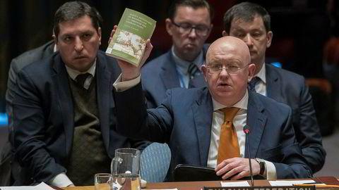 Russlands FN-ambassadør Vasilij Nebenzja holder opp et eksemplar av boken Alice i eventyrland mens han snakker i FNs sikkerhetsråd torsdag.