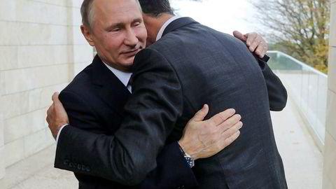 Russlands president Vladimir Putin, omfavner Syrias president Bashar al-Assad i Svartehavsbyen Sotsji mandag.