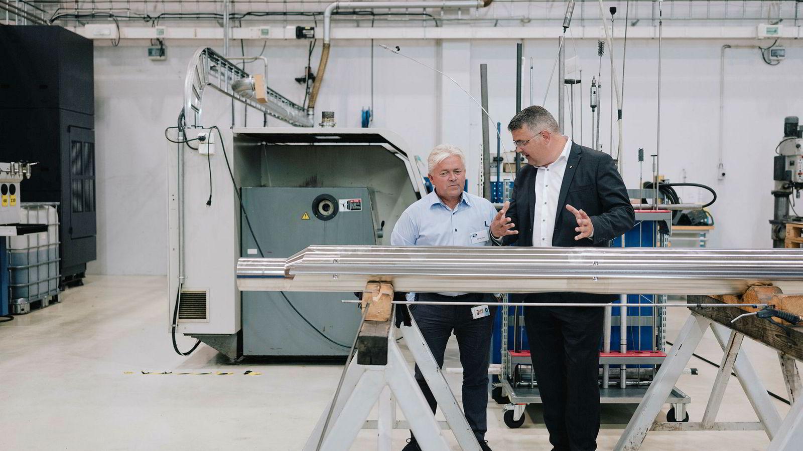 Rolf Egil Håland, daglig leder i oljeservicebedriften PTC (til venstre) viser frem nytt brønnutstyr for olje- og energiminister Kjell-Børge Freiberg (Frp) hos underleverandøren GMV på Forus.