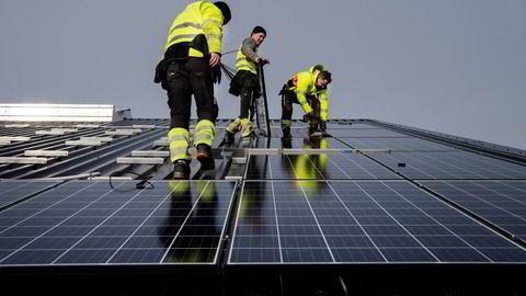 Torbjørn Kverneland (i midten), monterer solceller sammen med Kim André Vagle, André Hoftun sjekker monteringen med vater. Foto: Marie von Krogh