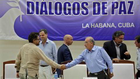Den colombianske regjeringens sjefforhandler, Humberto de la Calle (t.v.), håndhilste på sin motpart fra FARC, Ivan Marquez, etter at de nylig skrev under en avtale om å avvæpne geriljagruppen. Nå er også fredsavtalen mellom staten og geriljaen klar. Arkivfoto: Enrique De La Osa / Reuters / NTB scanpix