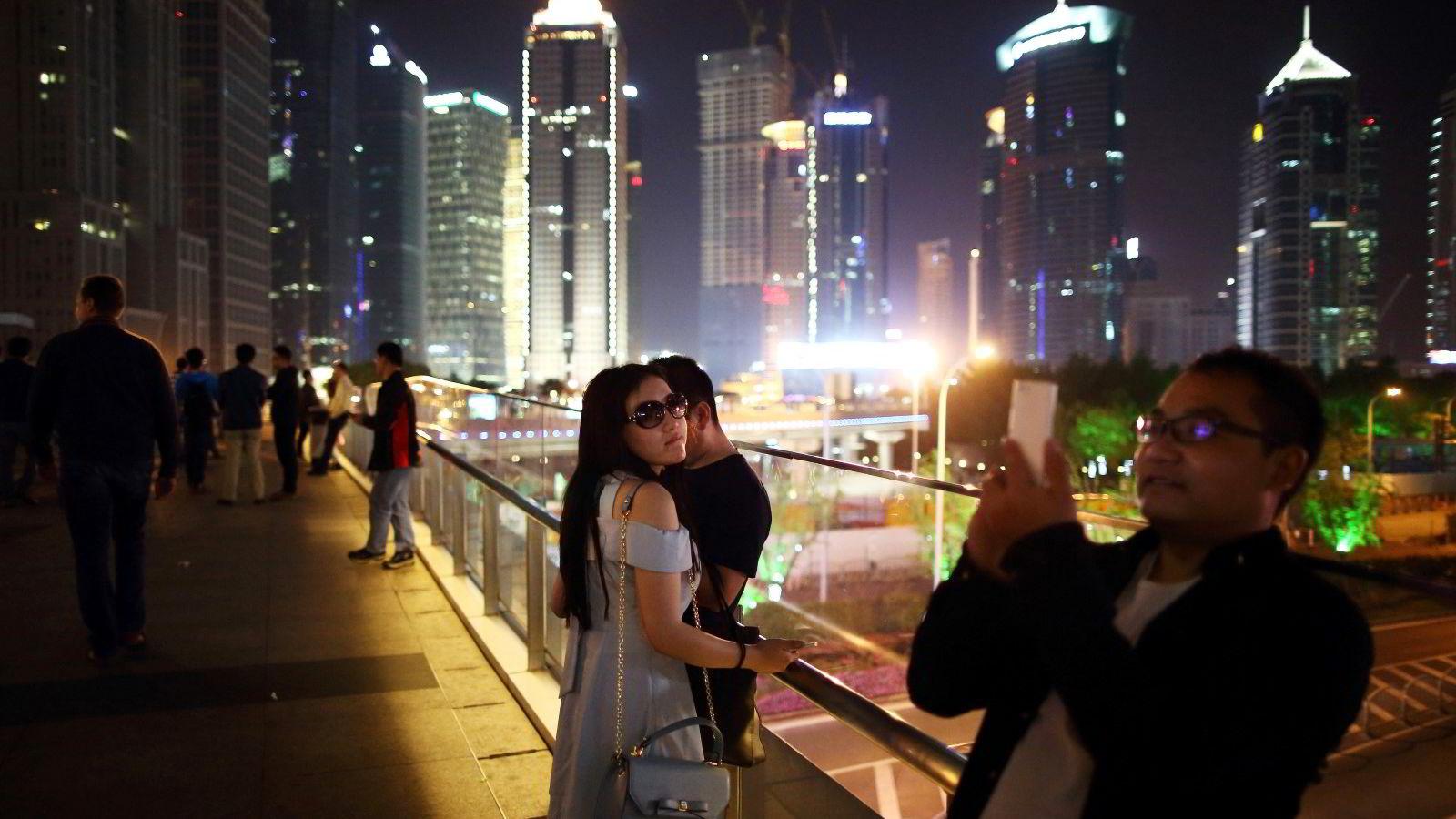Goldman Sachs og Franklin Templeton tror det snur i Brics-landene. Illustrasjonsfotoet viser en mann som tar bilder med sin smarttelefon mens folk rusler rundt i Lujiazui-distriktet i Shanghai. Foto:  Tomohiro Ohsumi/