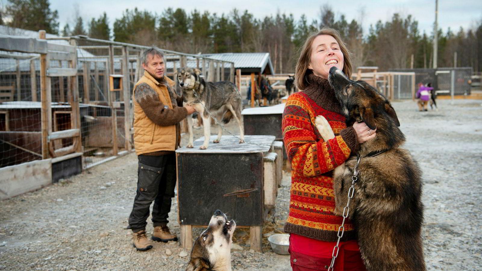 Kokk Johnny Trasti og hundekjører Trine Lyrek i hundegården med Neos og Vans, to av 79 alaskahusky hunder i selskapet Trasti & Trine utenfor Alta i Finnmark. I bakgrunnen hilser datteren Hanne Lyrek på en av hundene.