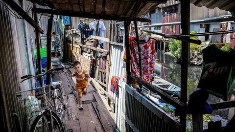 En gutt leker i gangområdet til et hus på elvebredden ved Xuyen Tam-kanalen i Ho Cho Minh City i Vietnam.