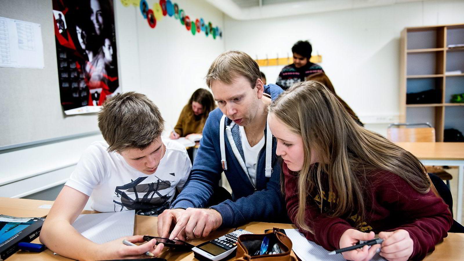Ungdomsskoleelevene Gustav Tolstrup Christensen (15) og Sara Brown Bergly (15) får undervisning i videregående-matematikk av lærer Skage Hansen. Foto: Klaudia Lech