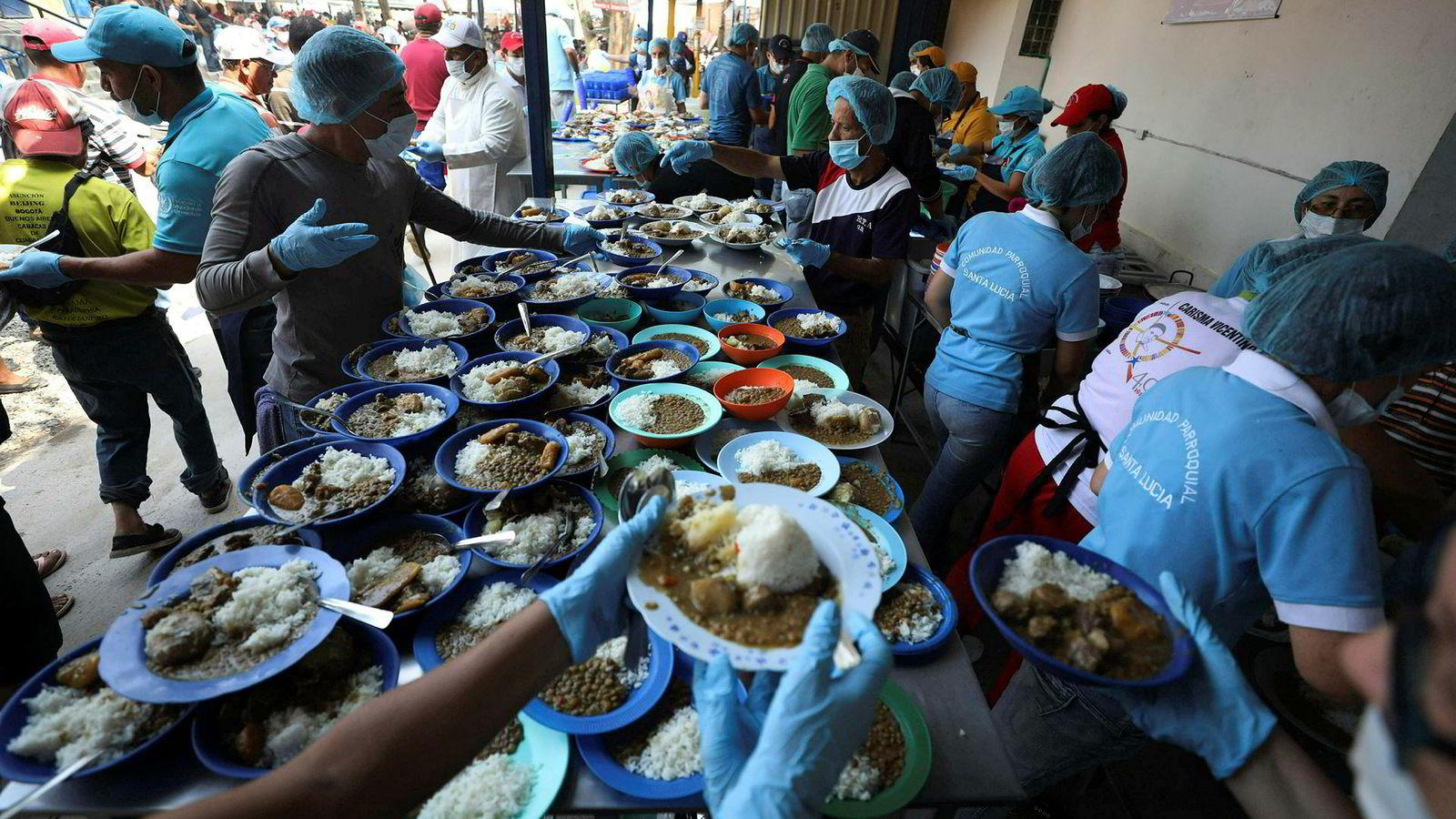 Frivillige deler ut gratis lunsj til venezuelanske migranter i et flyktningmottak i La Parada i Colombia, ved grensen til Venezuela. Millioner av venezuelanere har forlatt hjemlandet, som mangler mat, medisiner og andre basisvarer.