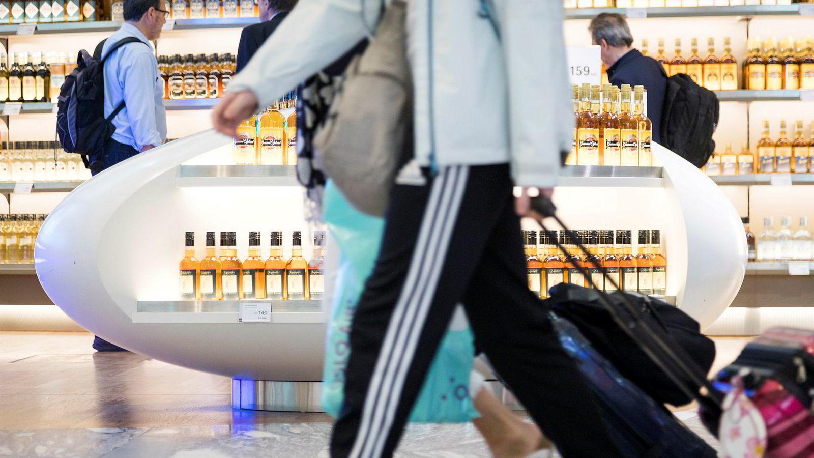 Reisende passerer taxfreebutikken i avgangshallen på Oslo lufthavn Gardermoen.