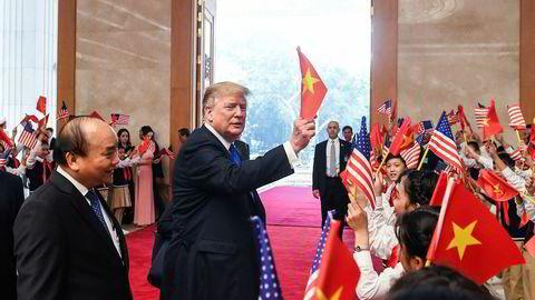 USA president Donald Trump vifter med det vietnamesiske flagget før et møte med Vietnams statsminister Nguyen Xuan Phuc (til venstre) i Hanoi tirsdag. Onsdag møter Trump Nord-Koreas leder Kim Jung-un