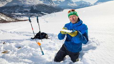 Torben Rognmo, skredobservatør i NVE, studerer et snølag på vei opp mot Tromsdalstinden. Han kaller vurderinger av snø og skred en evigvarende læringsprosess der han hver gang stiller seg selv nye spørsmål. Foto: Gunnar Lier
