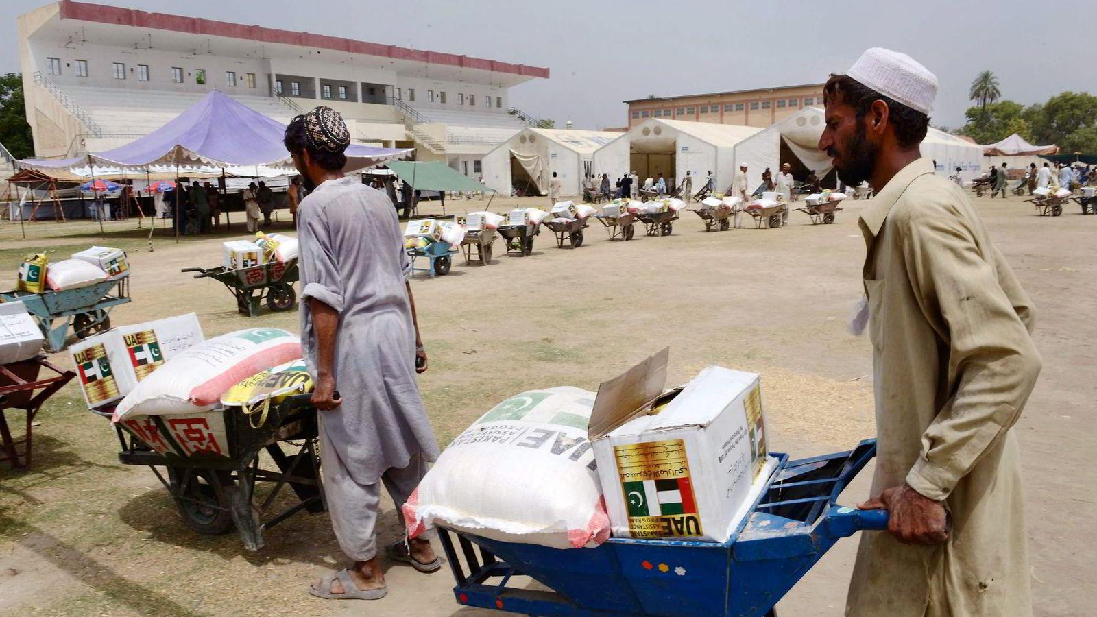 NY METODE. Verdens matvareprogram (wfp) og MasterCard samarbeider om et «digital mat»-prosjekt, med mål om å dele ut en tredjedel av hjelpen på mer effektivt vis innen 2015. Her fra Bannu i Pakistan, der WFP distribuerer maten på tradisjonelt vis. Foto: A Majeed, Afp Photo/NTB Scanpix