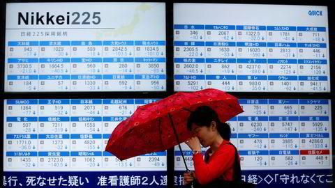 En dame med paraply passerer et meglerhus i Tokyo med en skjerm som viser aksjekurser. Arkivfoto: Toru Hanai/Reuters/NTB scanpix