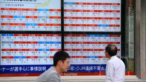En mann kikker på en elektronisk tavle med aksjekurser fra Tokyo-børsen. Foto: Kazuhiro Nogi/AFP Photo/NTNB scanpix