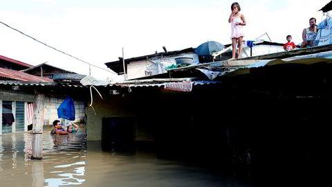 Et par tar seg gjennom vannmassene for å kjøpe drikkevann etter at tyfonen  Mangkhut rammet Filipinene i helgen og oversvømmet lavtliggende områder. Bildet er fra Calumpit i Bulacan-provinsen nord for Manila.