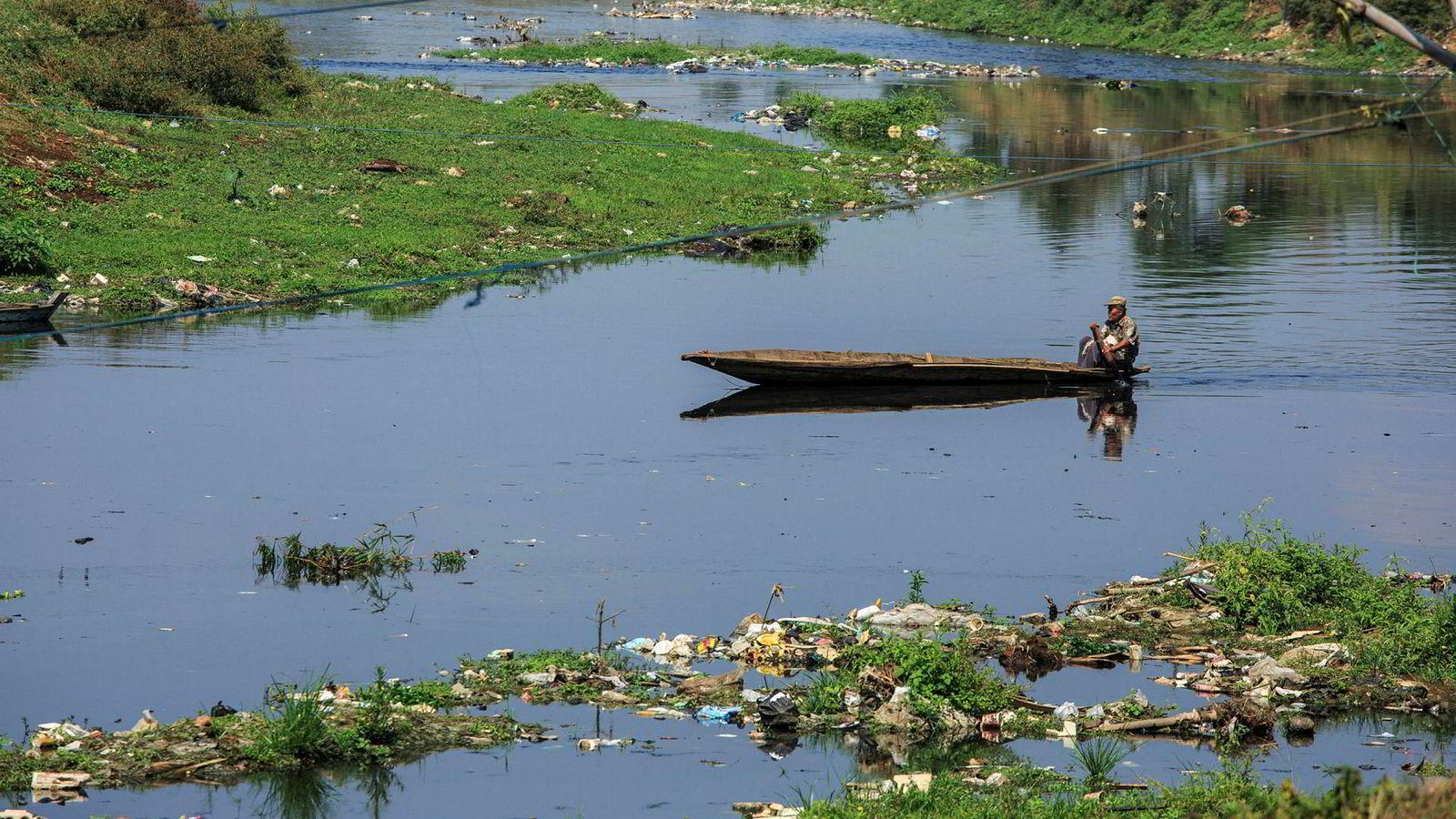 Store mengder søppel skjemmer det som kunne vært idylliske omgivelser for mannen i båten på Citarum-elven utenfor Bandung.