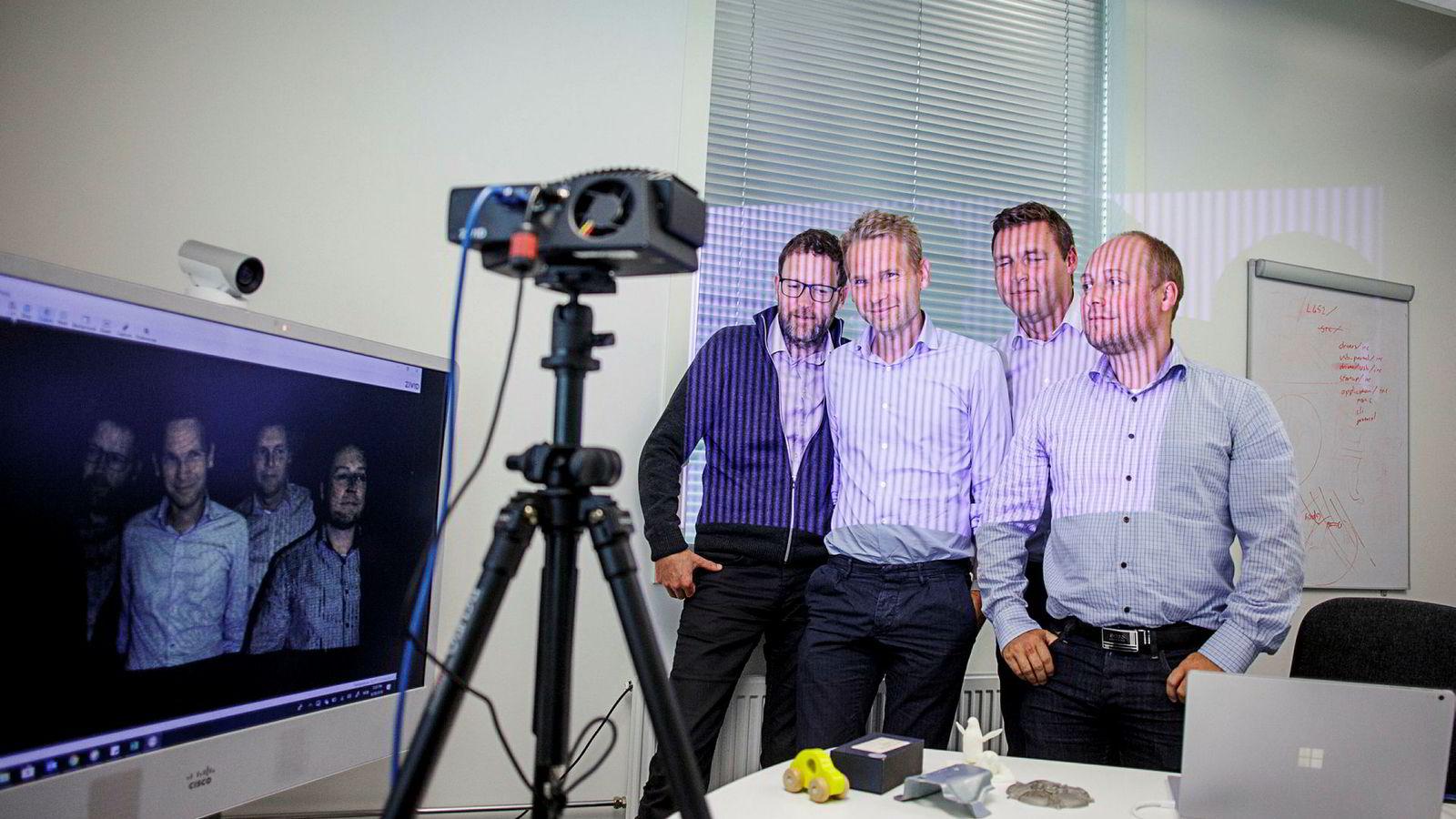 3D bildet på skjermen er laget ved å sende «strukturert lys» fra robothodets ene øye, og lese det av med det andre. Skjermen viser (fra høyre) Øystein Skotheim gründer og programvareutvikler, Arild Ulfeng, leder for ingeniørteamet, Thomas Embla Bonnerud, toppsjef, nylig ankommet fra Nordic Semiconductor og Henrik Schumann-Olsen, gründer og leder til nå.
