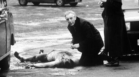 Pater Alec Reid gir korporal David Howes den siste olje. Howes og kollegaen ble drept av en rasende mobb, etter at de kjørte feil og havnet i et begravelsesfølge for ofrene etter et attentat mot en IRA-begravelse.