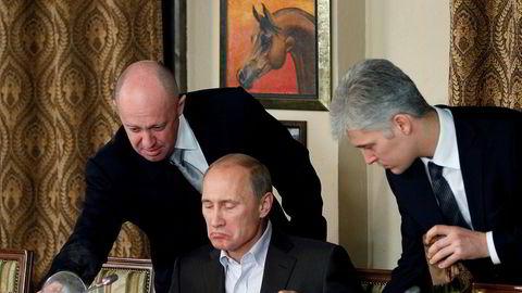Jevgenij Prigozjin (til venstre) omtales ofte som Vladimir Putins kokk. Her serverer han presidenten på en restaurant i Moskva.
