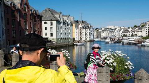 Asiatiske turister foreviger minner ved Brosundet i Ålesund.