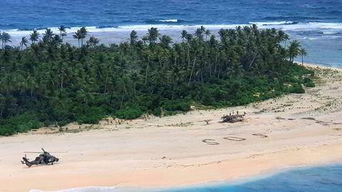 Et australsk helikopter landet på stranda der tre menn ble funnet etter å ha skriblet «SOS» i sanden.