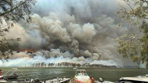 Brannrøyk dekker himmelen over småbåter som er trukket på land ved Lake Conjola i Australia torsdag. Turister evakueres fra utsatte steder sørøst i landet. Foto: Robert Oerlemans / AP / NTB scanpix