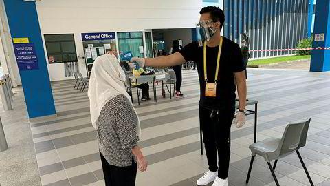 En velger i Singapore får temperaturen målt før hun kan avlegge stemme