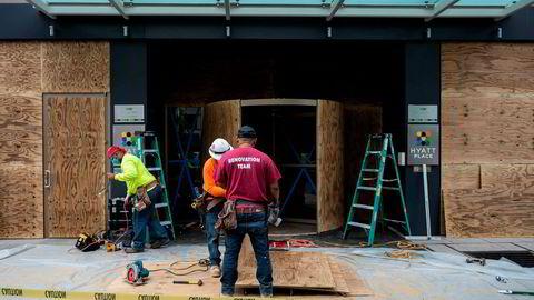 Arbeidere i Washington, D.C. setter opp kryssfinérplater på Hyatt Place Hotel.