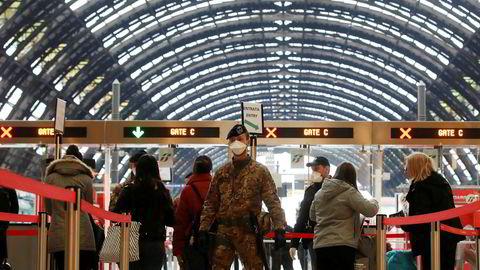 Politi og soldater sjekke passasjerer som forlater Milans hovedtogstasjon. Bildet er tatt mandag 9. mars.