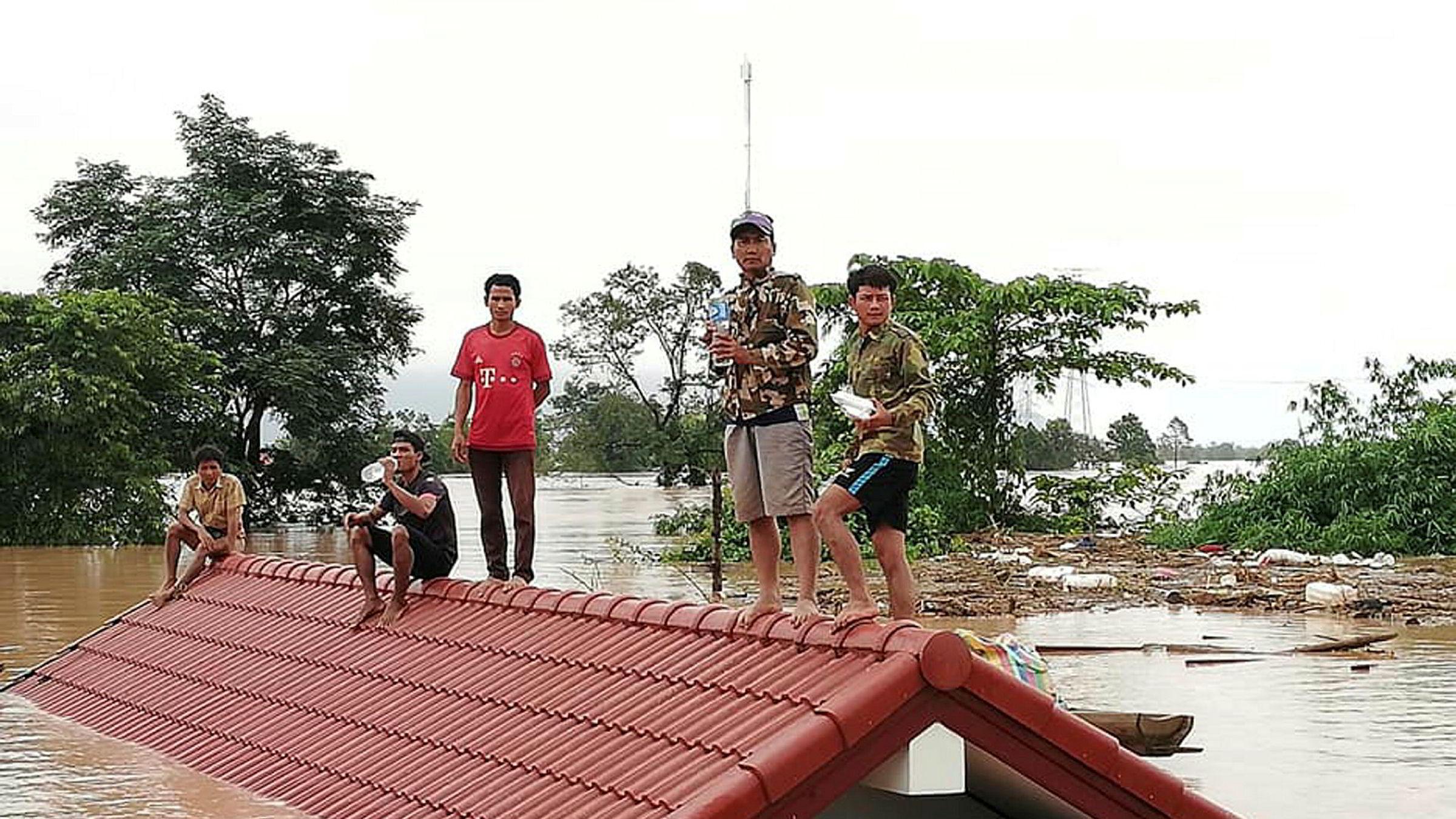 Stillbilde fra et TV-opptak som viser folk som evakueres fra det oversvømmede området sør i Laos.