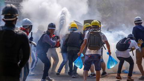 Demonstranter bruker brannslukningsapparater for å beskytte seg mot tåregass i Yangon i mars i år. Protestene var svar på kuppet i februar.