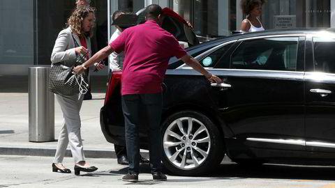 En sjåfør fra et delingsøkonomiselskap hjelper en passasjer inn i en bil på 6th Avenue i New York City.