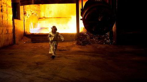 Varmeutstrålingen er formidabel når flytende mangan tømmes ved Sauda Smelteverk. En arbeider kledd i beskyttelsesdrakt henter ut en metallprøve for analyse.