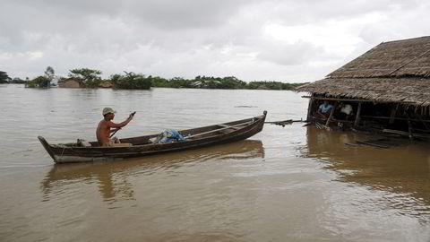 En mann bruker båt for å ta seg fram i en landsby utenfor Zalun ved elvedeltaet Irrawaddy i Myanmar. Foto: