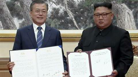 Sør-Koreas president Moon Jae-in (til venstre) og Nord-Koreas leder Kim Jong Un viser frem felleserklæringen de har signert.