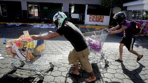 Motstand mot en pensjonreform har ført til store protester i Nicaraguas hovedstad, Managua. Bildet viser personer som har plyndret en butikk etter gateprotester.