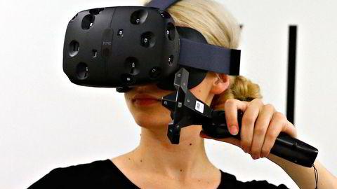 Köln, 5. august 2015: En kvinne prøver HTCs Vive virtuelle opplevelse under Gamescom-messen. Sensorene på utsiden av visiret gjør at man kan bevege seg naturlig i det fysiske rommet og få forflytningen gjenspeilet i det virtuelle rommet. Sensorene passer også på at man ikke går inn i noe ved å tegne opp røde streker i det virtuelle rommet. Foto: NTB Scanpix.