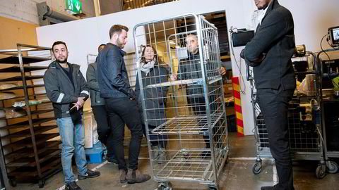 Matbutikken Meny på Bryn i Oslo bruker logistikkverktøy fra Shafi Adan (til høyre) og Arne Kvale (nummer tre fra venstre) i gründerselskapet Zoopit til å styre utkjøring til nettkundene. Traian Marius Dinca passerer Cathrine Laksfoss fra Schibsted Distribusjon med en tom tralle, mens sjåførene Zoopit Ali Goher Abbas (til venstre) og Naod Fissehaye (nesten skjult) venter på å kjøre matvarene hjem til folk.