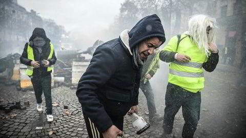 Tåregassen lå tykk over Champs Elysees i Paris lørdag formiddag.