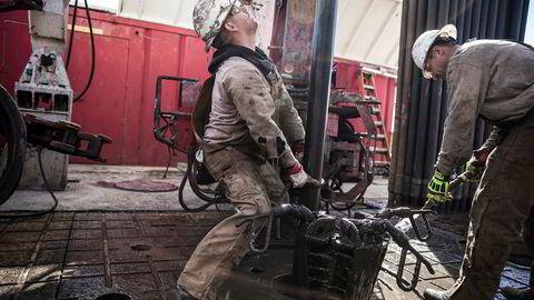 To riggarbeidere fra Sidewinder Drilling forsøker å koble fra hverandre et borerør på en borerigg utenfor Midland, Texas. USA er i ferd med å bli en stadig mer dominerende oljemakt.