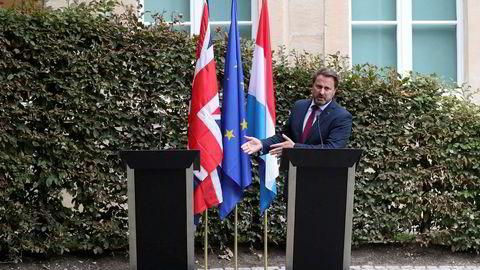 Luxembourgs statsminister Xavier Bettel peker på den tomme talerstolen der hans britiske kollega Boris Johnson skulle stått etter møtet mellom de to mandag.