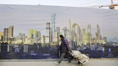 En skrotplukker går forbi en plakat som viser en plakat med bilde av finansdistriktet i Kinas hovedstad Beijing. FOTO: