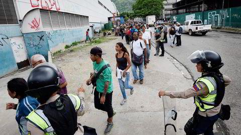 Politiet holder orden i en matkø i Caracas onsdag denne uken. Over 70 prosent av Venezuelas befolkningen lever i dag under fattigdomsgrensen. Foto: Juan Barreto/AFP/NTB Scanpix